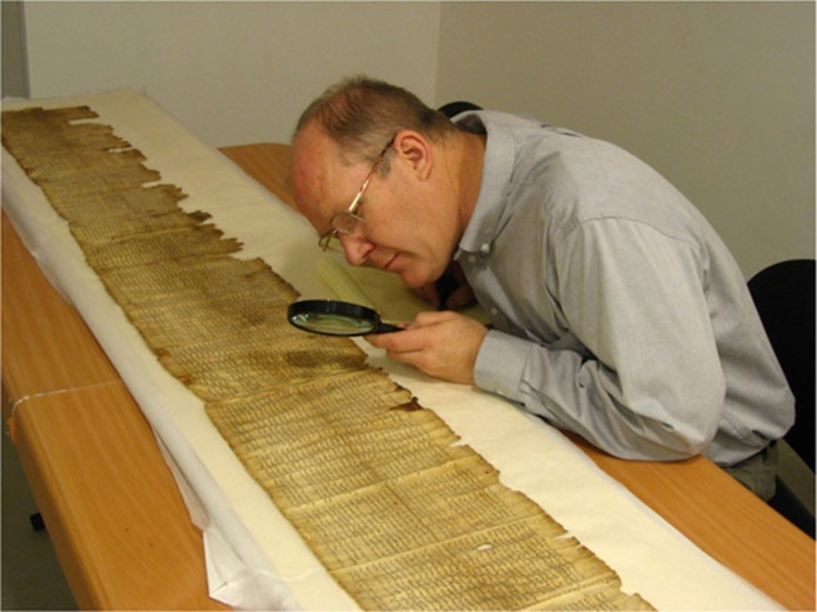 No, he's not a 2000 election worker looking for hanging chads. He is examining a scroll of Scripture!